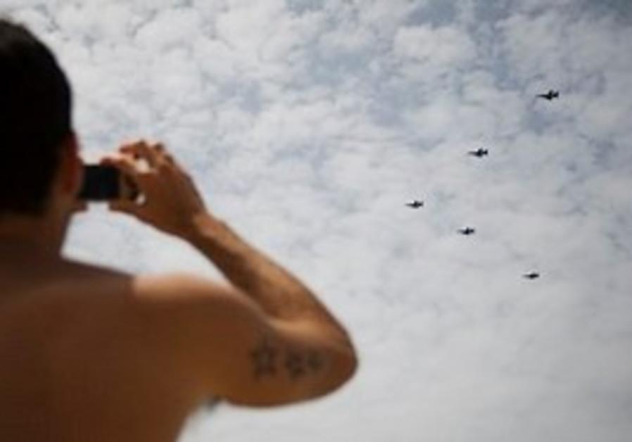 A beach goer watches am aerial demonstration