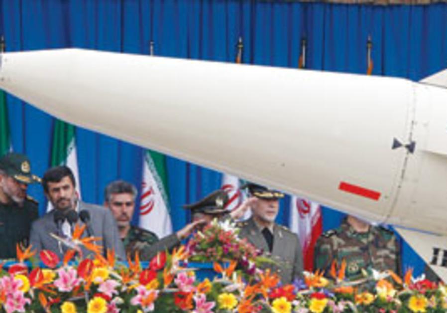 Iranian President Mahmoud Ahmadinejad watches as a