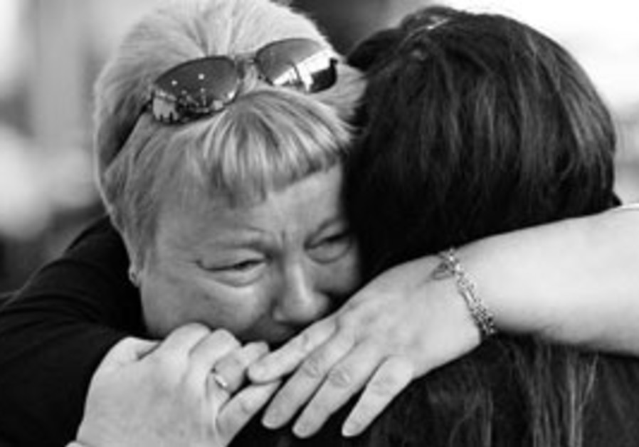 A woman cries as she hugs her daughter arriving ye