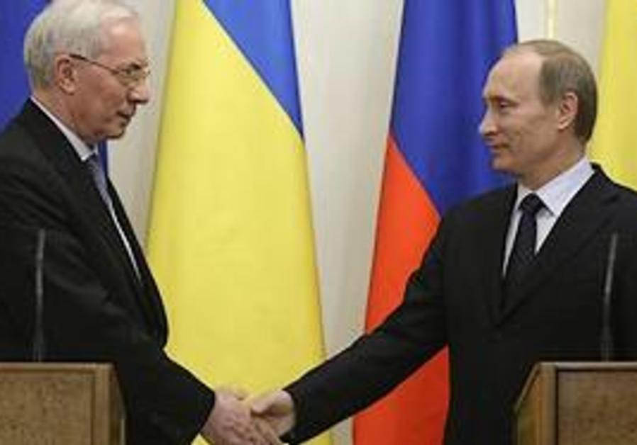 Russian Prime Minister Vladimir Putin, right, shak