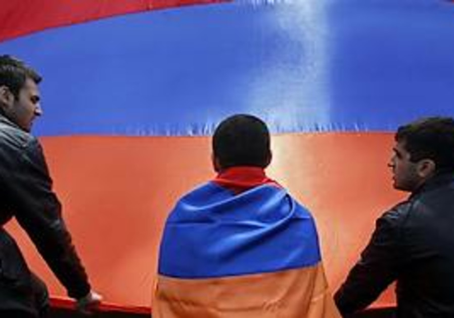 People sit in front of an Armenian flag during a r