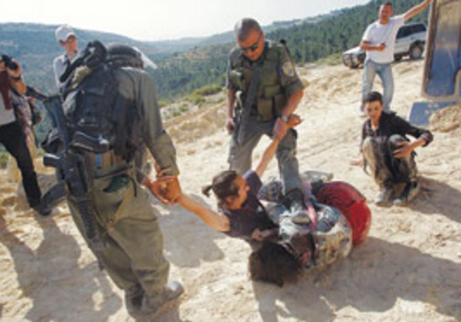 Border Policemen drag a protestor from a bullfozed