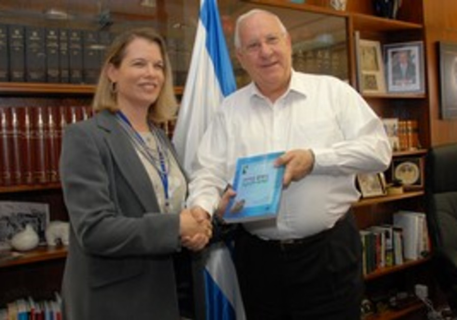 Rivlin receives a copy of the latest edition of 'W