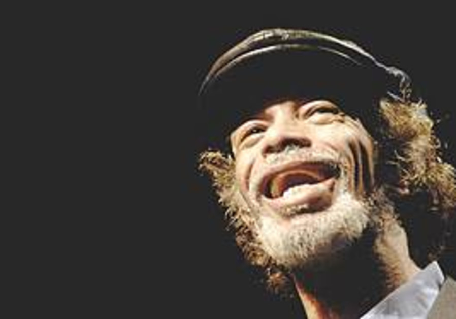 Gil Scott Heron smiles while on stage in front a p