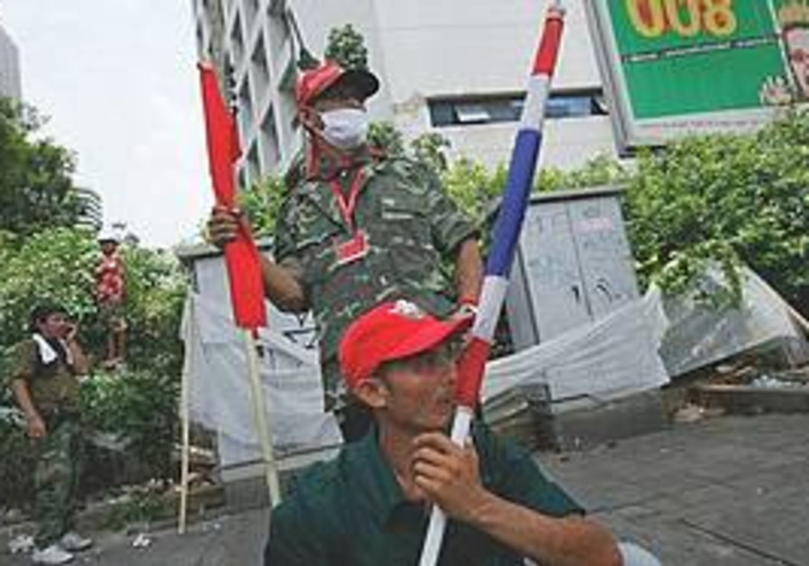 Anti-government protesters guard at a makeshift ba