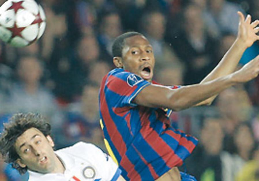 FC BARCELONA'S Seydou Keita (right) clears the bal