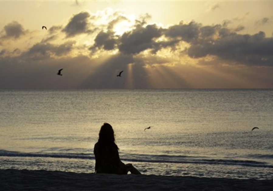 A woman meditates on the beach in Miami Beach, Flo