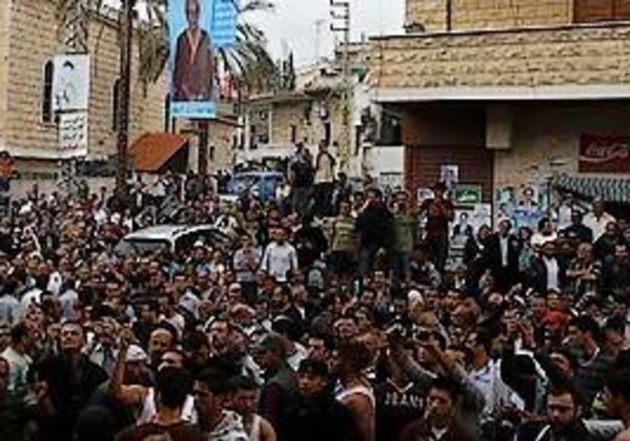 Lebanese villagers gather near the body of Egyptia
