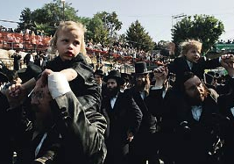 Haredim carry their sons for their first haircuts