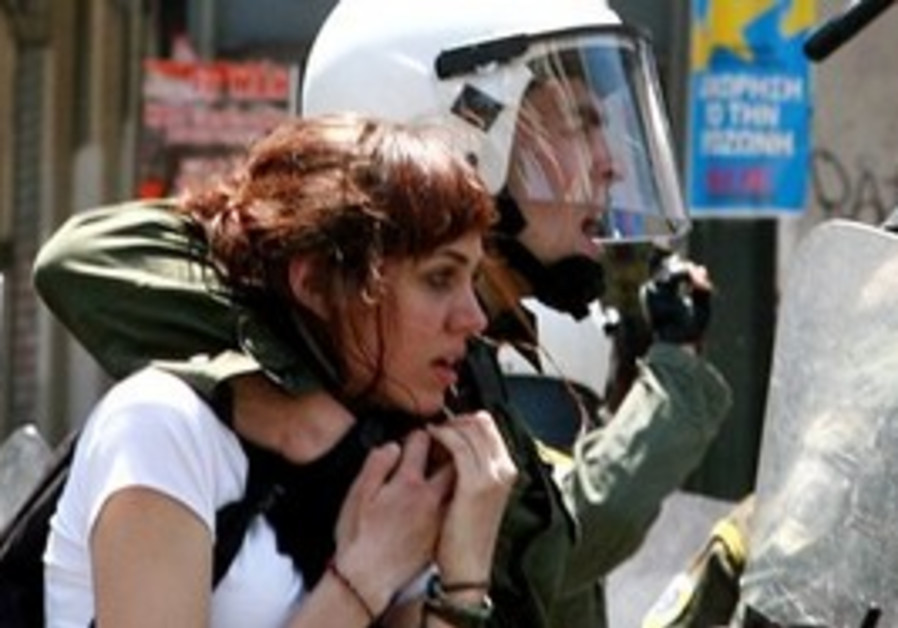 A riot police holds a young woman after her arrest