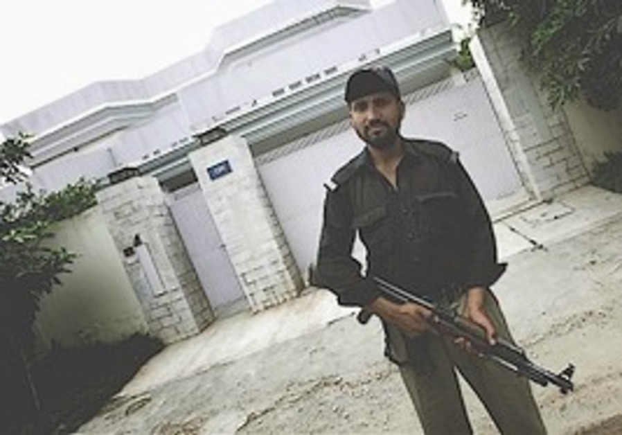 Pakistani police officer stands outside house owne