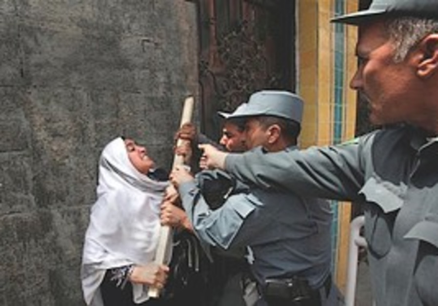 Afghan policemen scuffle with a protester as she t