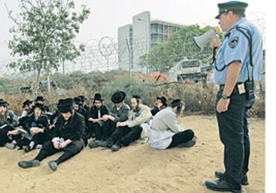 Haredim sit on the ground next to a policeman in p