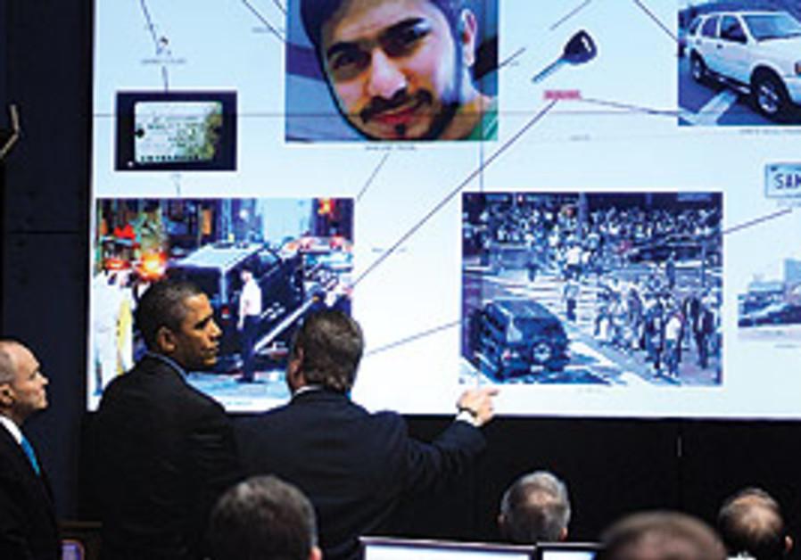 PRESIDENT BARACK OBAMA listens to a briefing by Ne