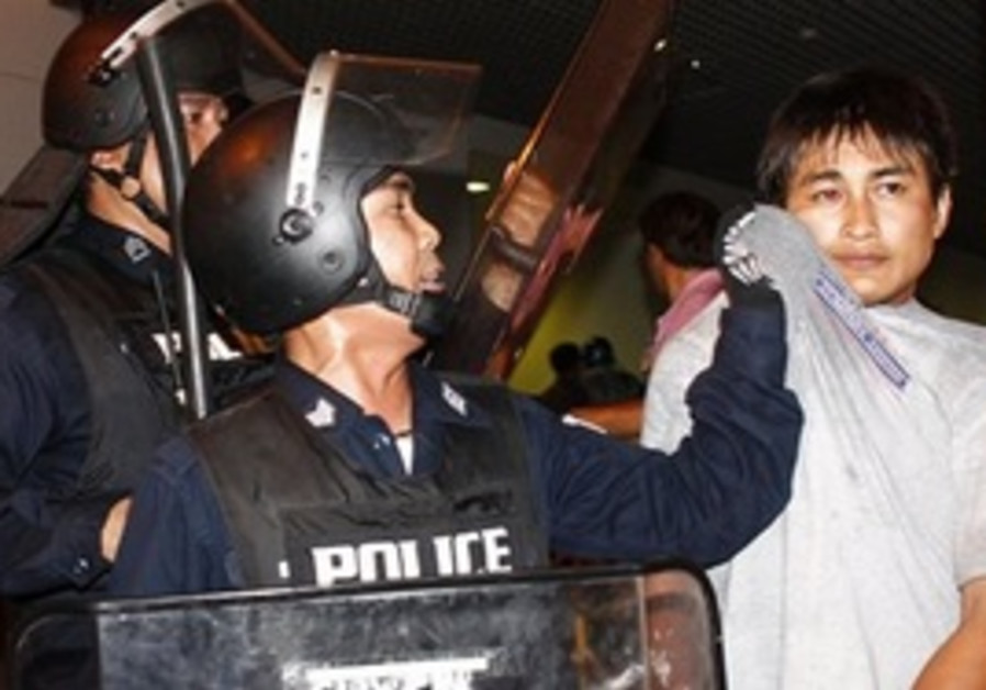 Thai riot police detain protester.