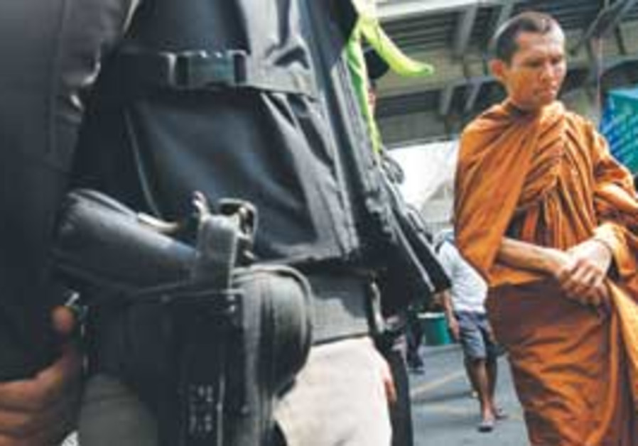a monk walkign past a policeman in bangkok