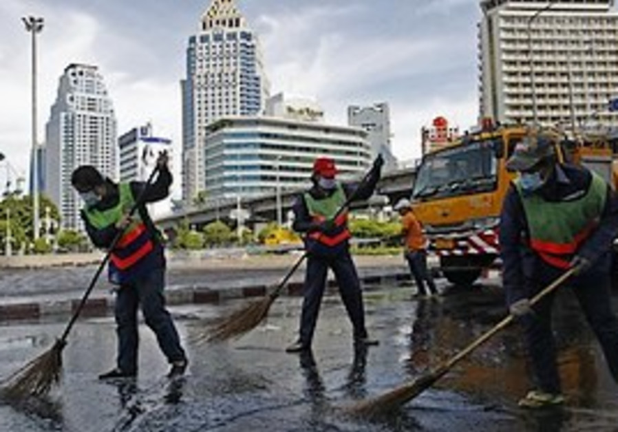 Bangkok, Cleaners sweep the grounds that were occu