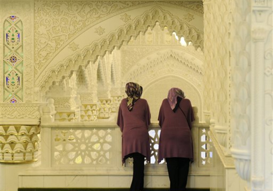 Female visitors look at the architecture of the Om