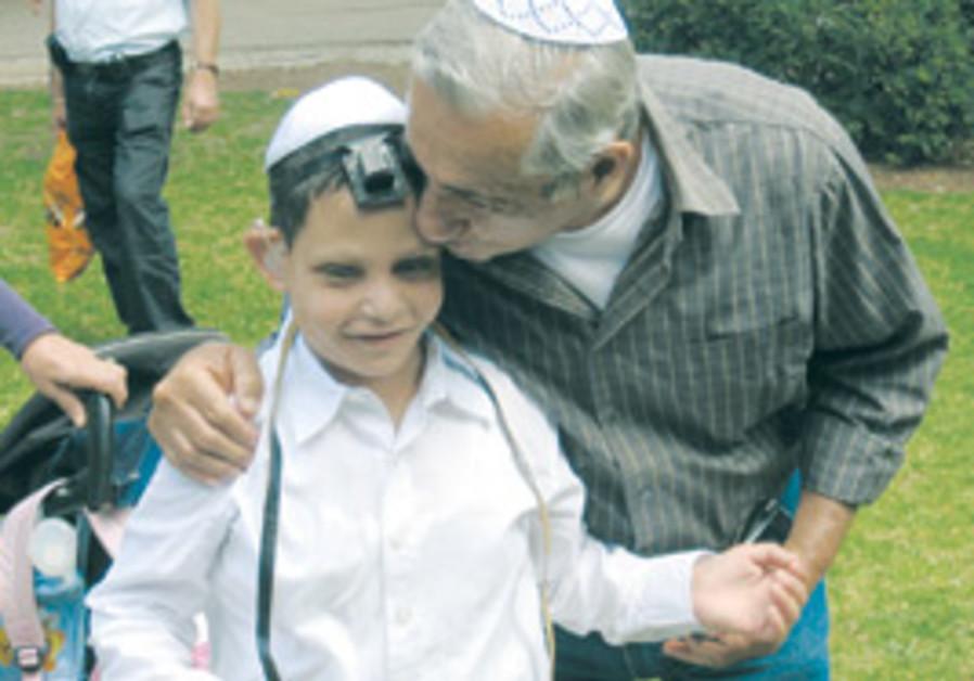 A BOY celebrates his bar mitzva with a family memb