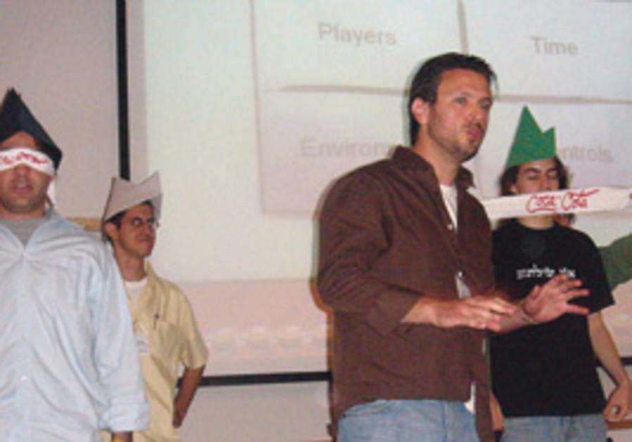GAME EXPERT Ofir Katz (middle) gives a presentatio