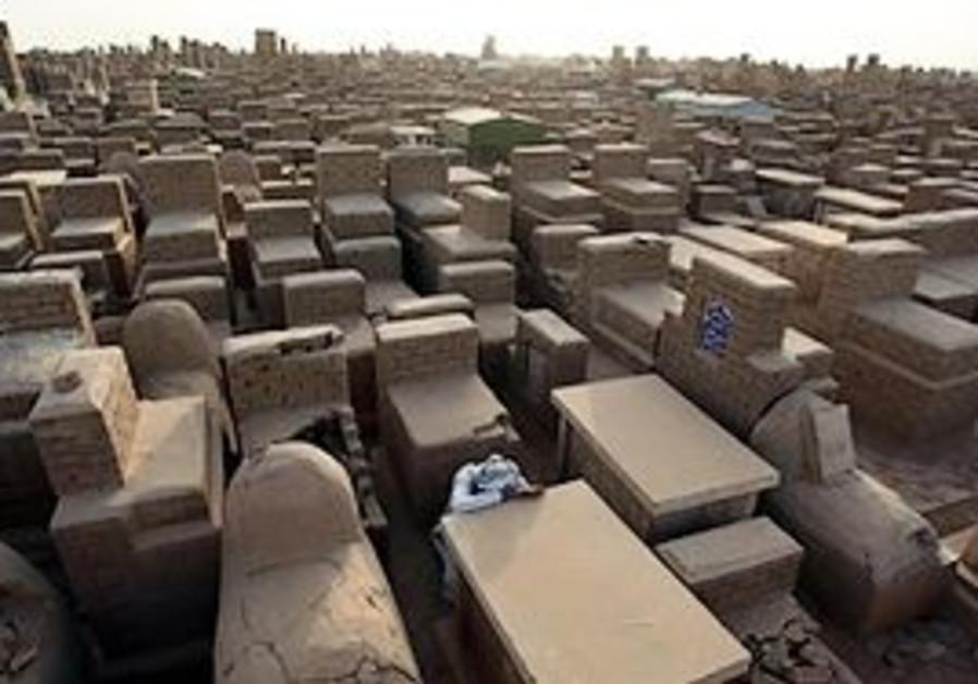 Mushtaq Wahab slumps the grave of his son, who was