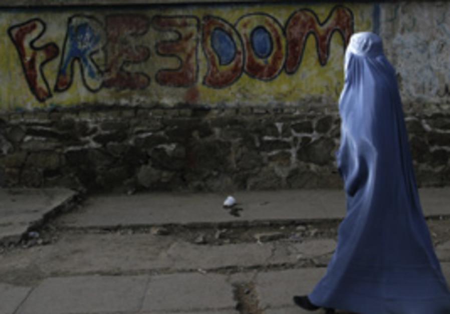An Afghan woman clad in a burqa walks in Herat, Af