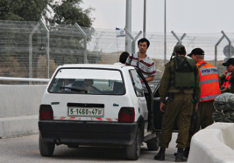 Soldiers inspect a Palestinian's car a the new che