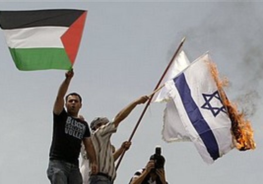 Protesters burn an Israeli flag during a demonstra
