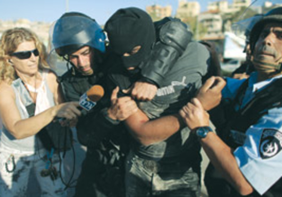 Police detain an masked Israeli Arab protester.