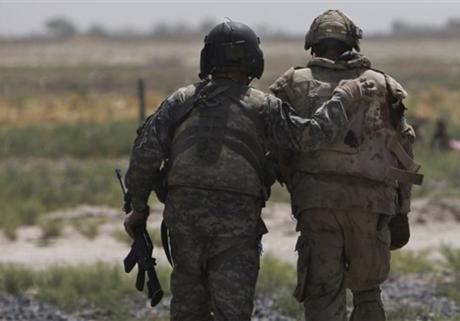 A medic with the US Army comforts an injured Canad