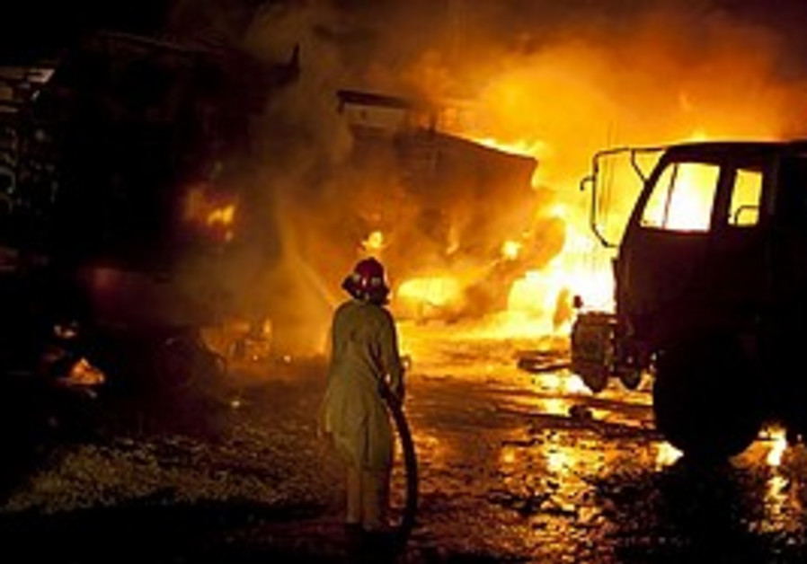 A Pakistani fireman tries to extinguish fire after