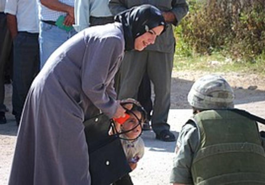 AN IDF soldier talks with a little Palestinian boy