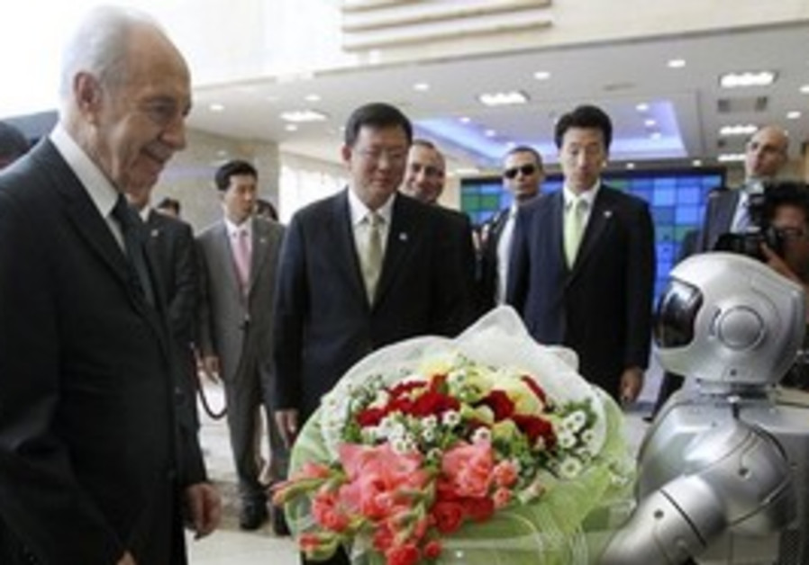 President Shimon Peres is greeted by a humanoid ro