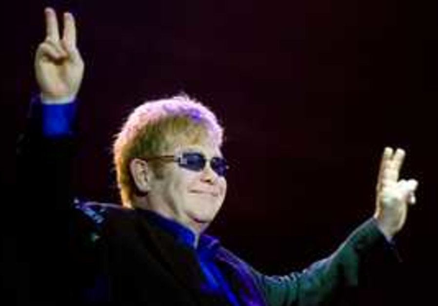 elton john gives peace signs at his concert in ram