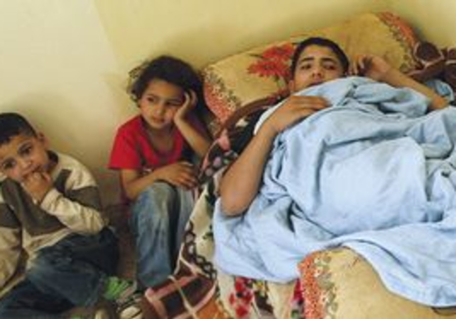 BED-RIDDEN ISSAM HELOU, 17, lies in the company of