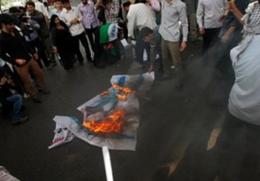 Iranian protestors burn a representative of an Isr