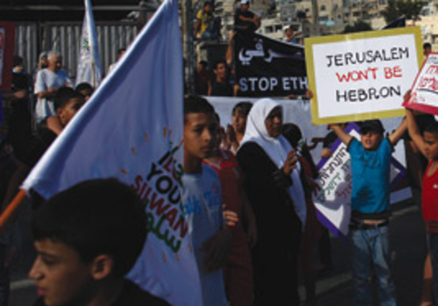 PALESTINIAN YOUTH hold up signs during a protest a