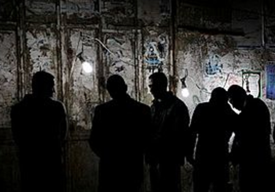 File photo - Palestinians stand near a generator d