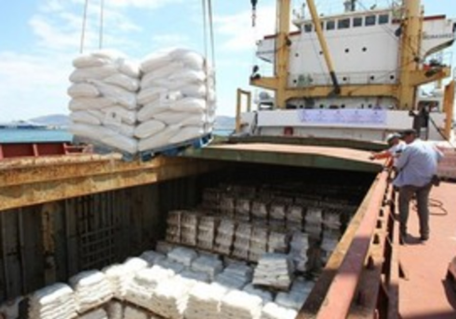 Workers load supplies on to a cargo ship at the La