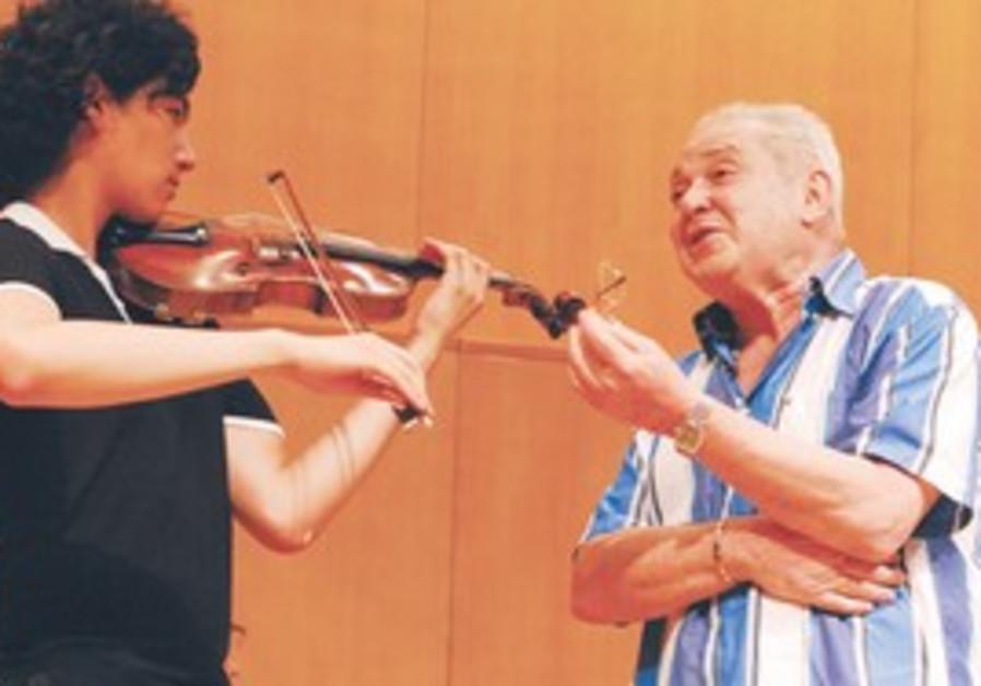 ONE OF three bows. Edward Grach (right) imparts so