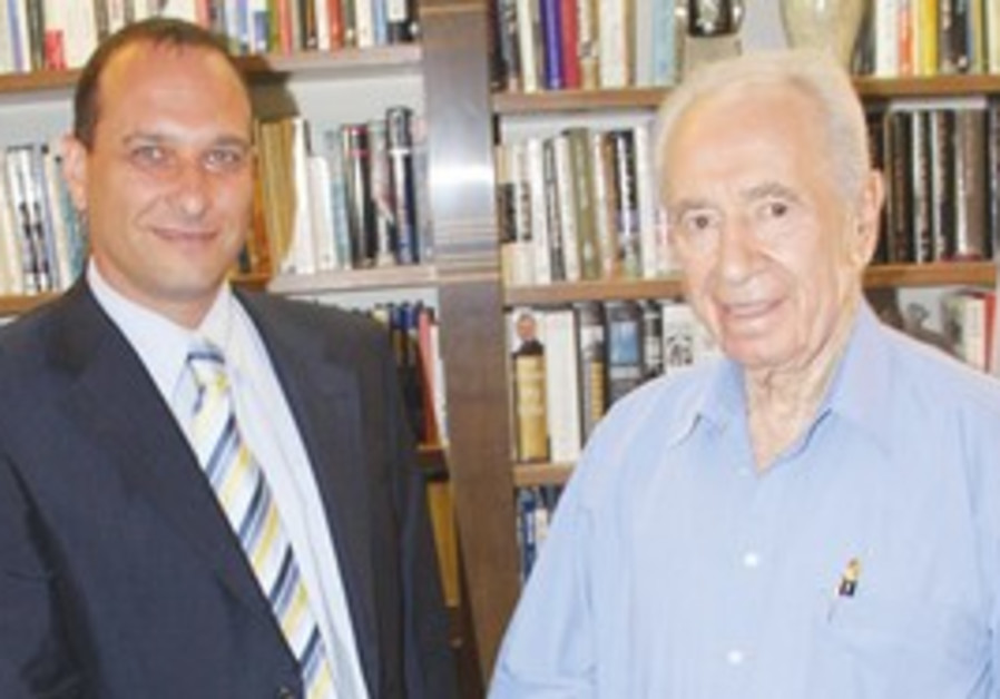 AMIR GILAT, the new Israel Broadcasting Authority chairman, shakes hands with President Shimon Peres