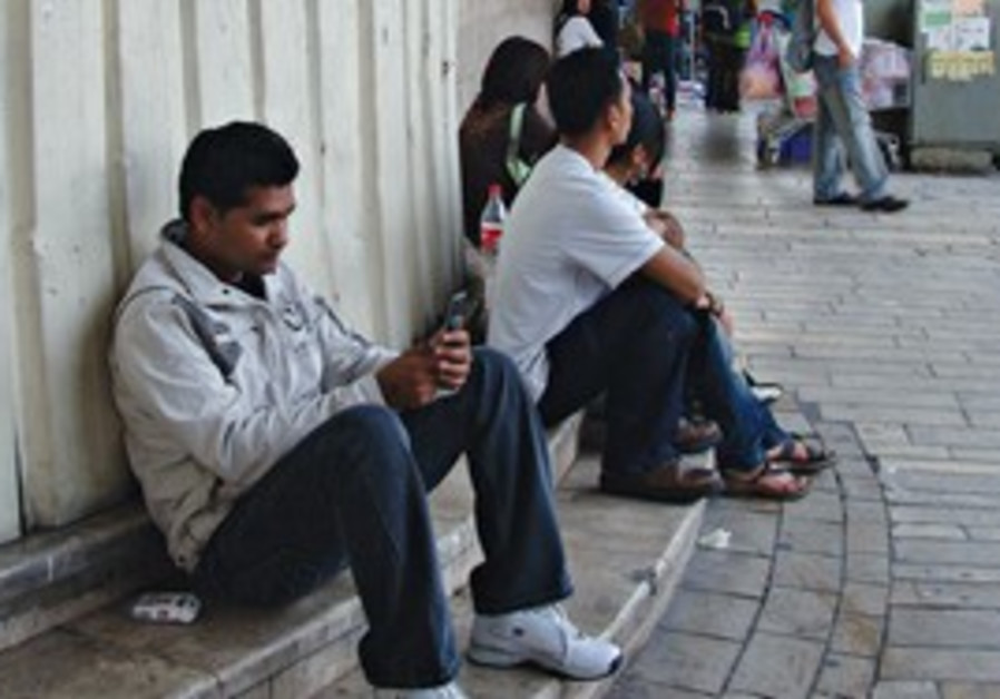 MIGRANT WORKERS outside the central bus station in Tel Aviv.