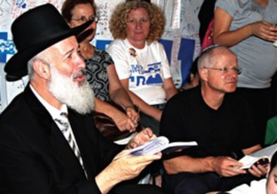 Outpouring of love. Chief Rabbi Yona Metzger and Noam Schalit at Tisha Be'av prayers.