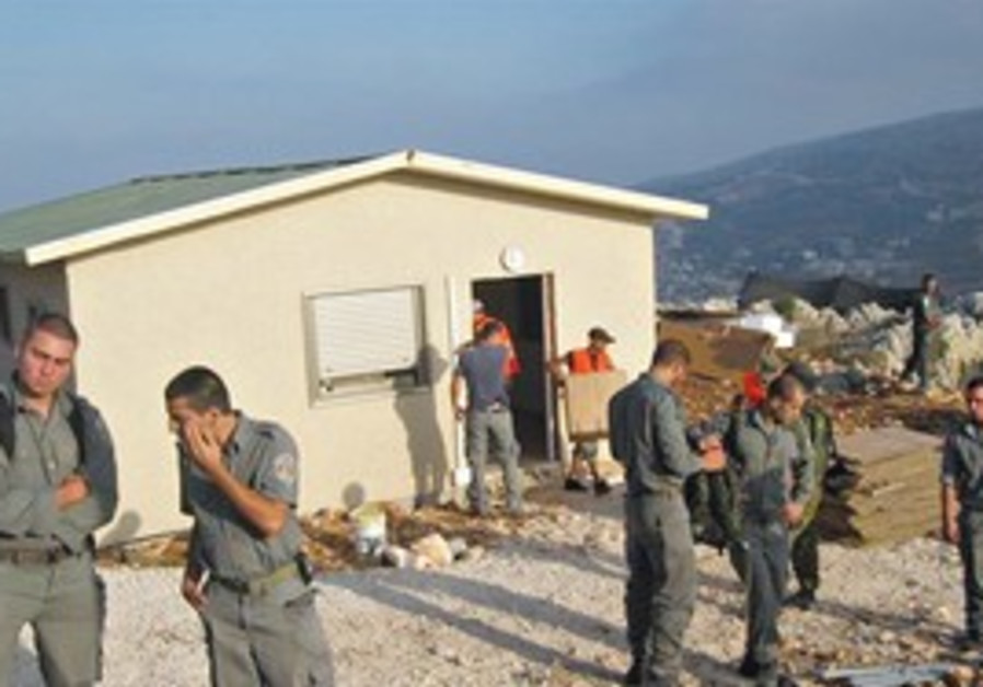 BORDER POLICE stand in front of a home near the Har Bracha settlement yesterday.