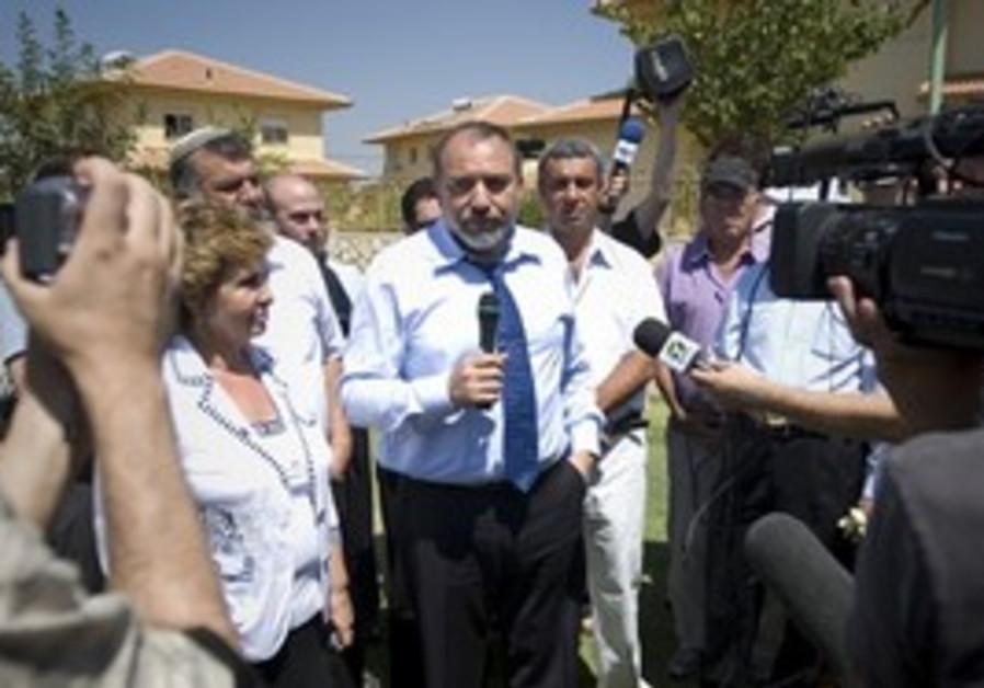 Israel's Foreign Minister Avigdor Lieberman, center, speaks during a visit to the West Bank settleme