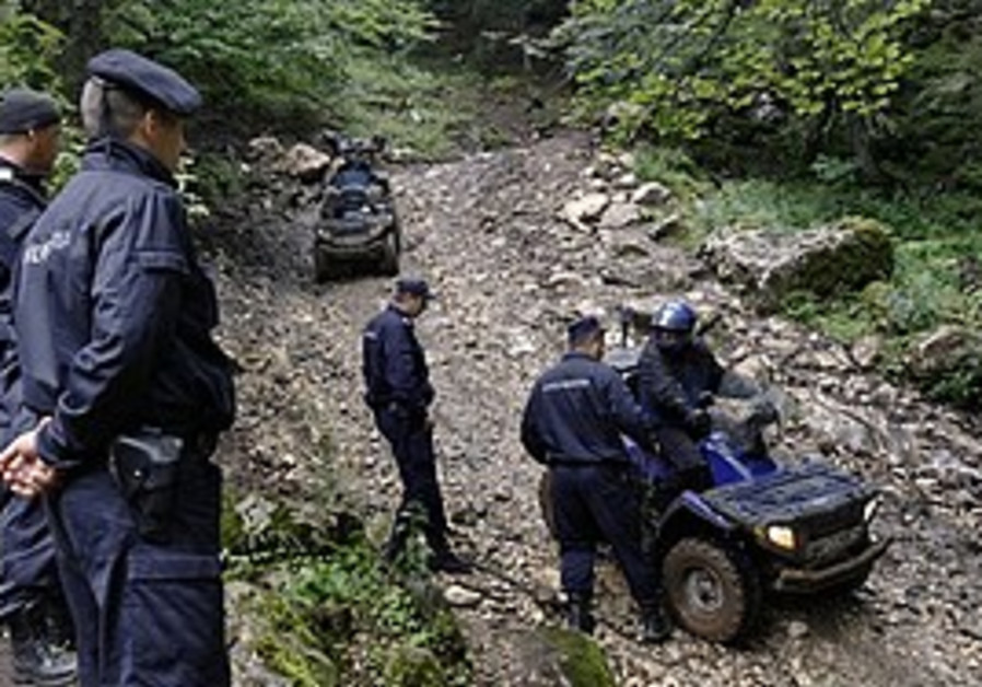 Crash investigators on mountain path near the Transylvanian town of Bran, Romania, Tuesday.