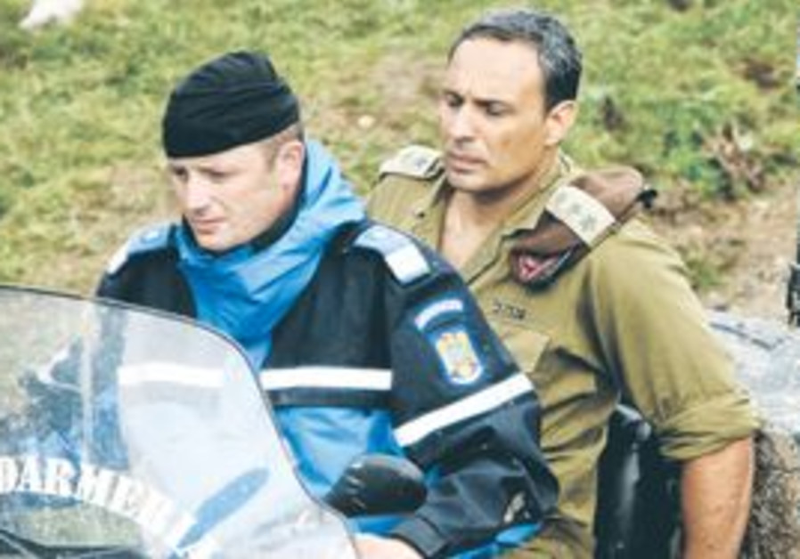 A ROMANIAN gendarme drives Israeli attaché Col. Shlomi Cohen down a mountain path near the crash sit