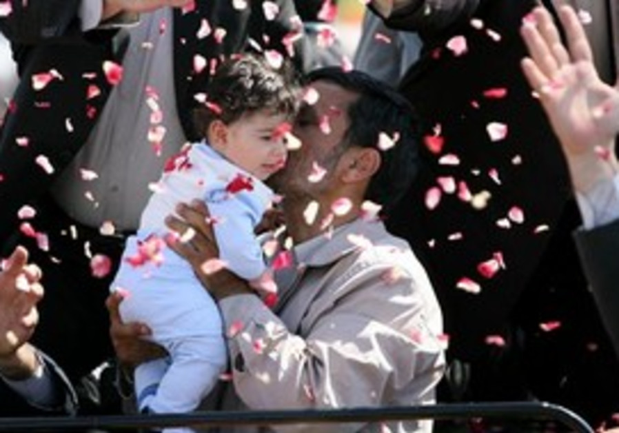 Ahmadinejad hugs an Iranian child in 2009 file photo