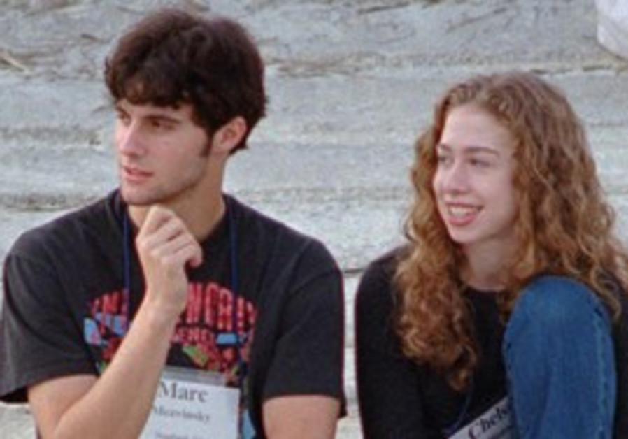 THIS 1996 file photo shows Chelsea Clinton sitting with Marc Mezvinsky in Hilton Head Island, S.C. C