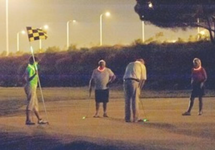 Golfers playing a night round at the Caesarea Golf Club.